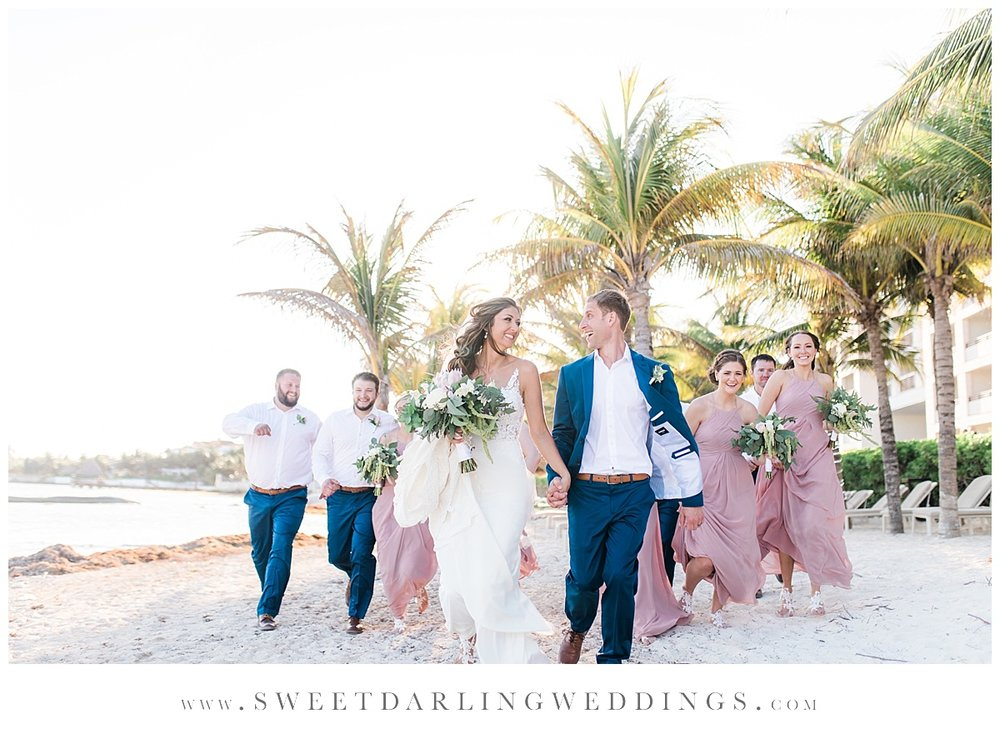 Fun bridal party portrait with palm trees at Secrets Silversands
