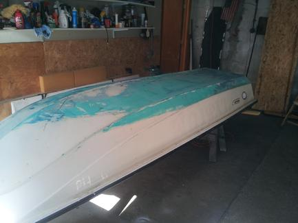 With the boat flipped over and before sanding.