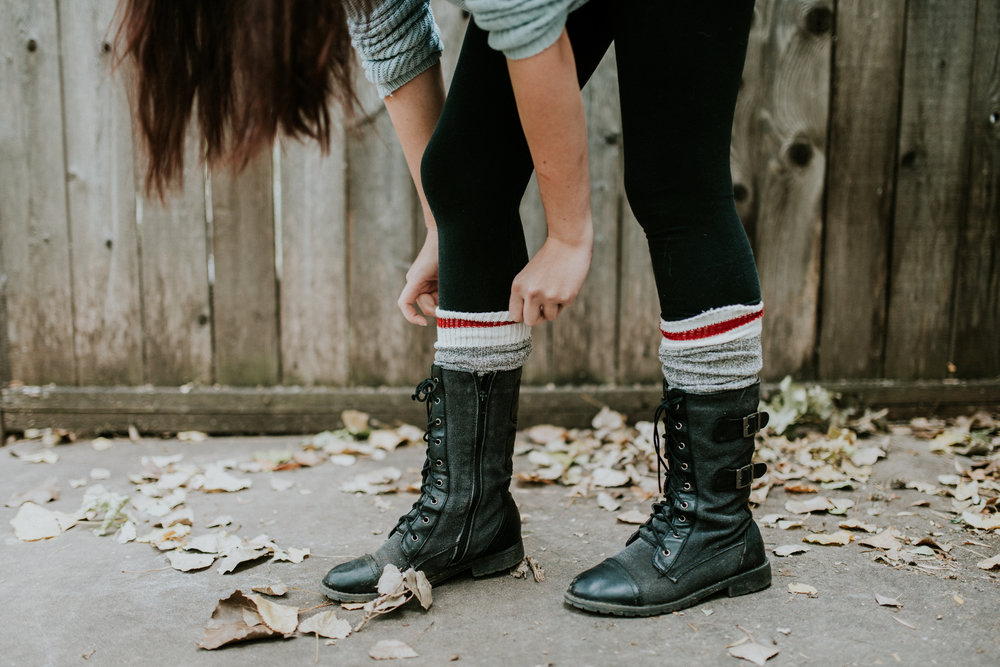 Girl bending down to tuck wool socks into boots during a commercial branding photoshoot