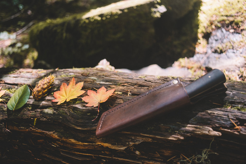 Commercial branding shoot showing wood knife in leather case with fall leaves around it