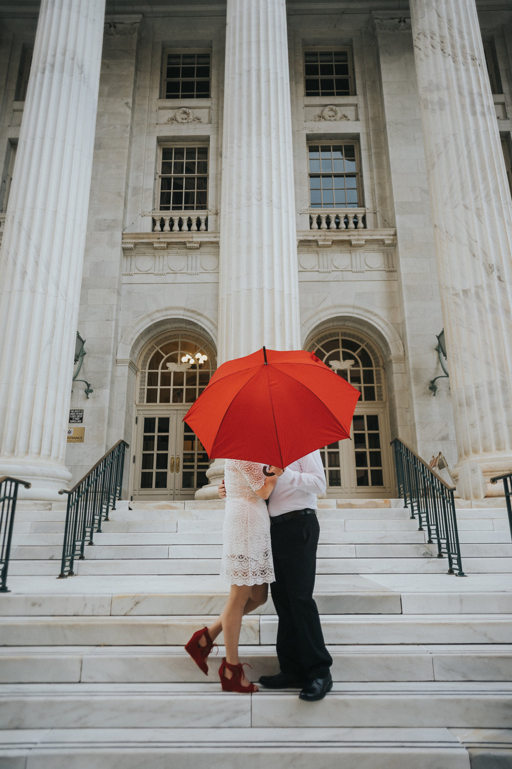 Romantic downtown Denver engagement photoshoot.  Couple kissing behind red umbrella