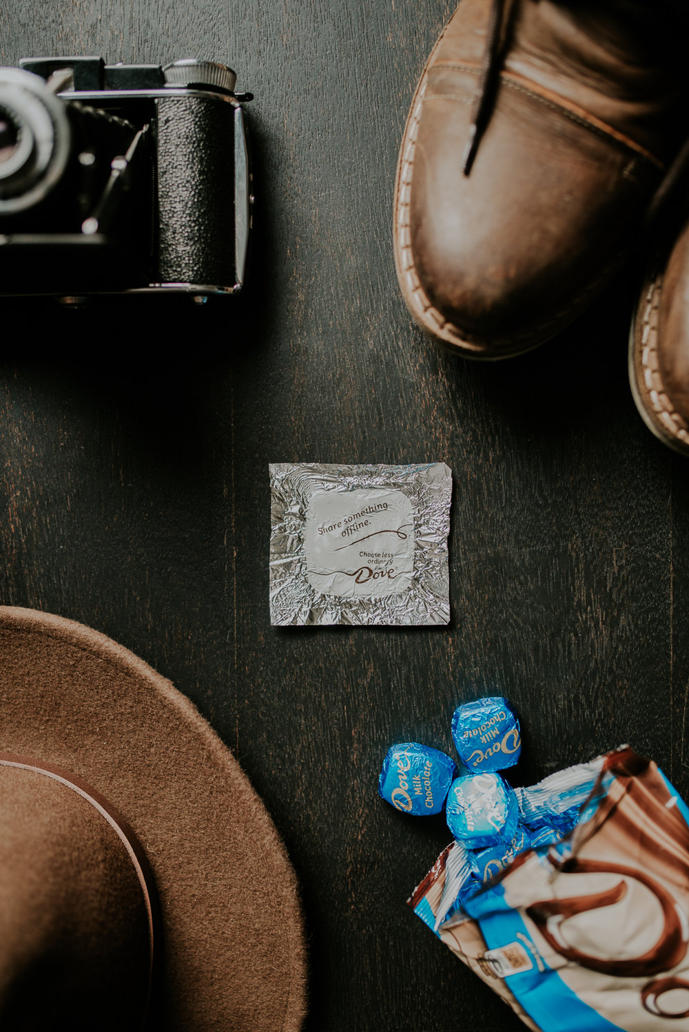 Overhead shot showing Dove Chocolate wrapper in the middle, boots, camera and hat on the outer edges of frame.