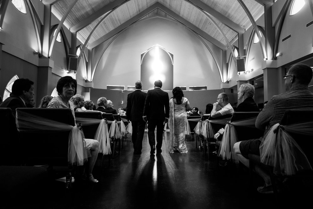 Romantic wedding couple holding hands at alter looking down the isle
