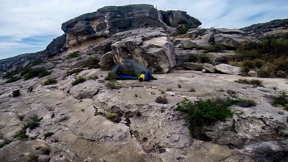 Camp below the big cliff that looks like a face carved in stone.