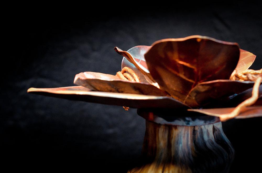 Bloem van metaal op een sokkel van appelhout.