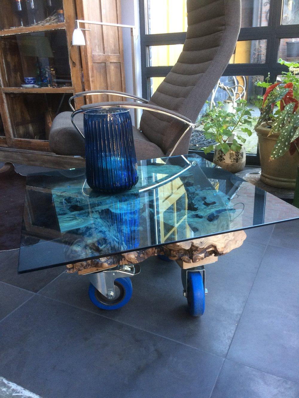 Olijfhouten Salontafel met blauwe glasplaat, het hout is 400 jaar oud en de tafel heeft drie industriële wielen. Afmeting 60 x 60 cm.