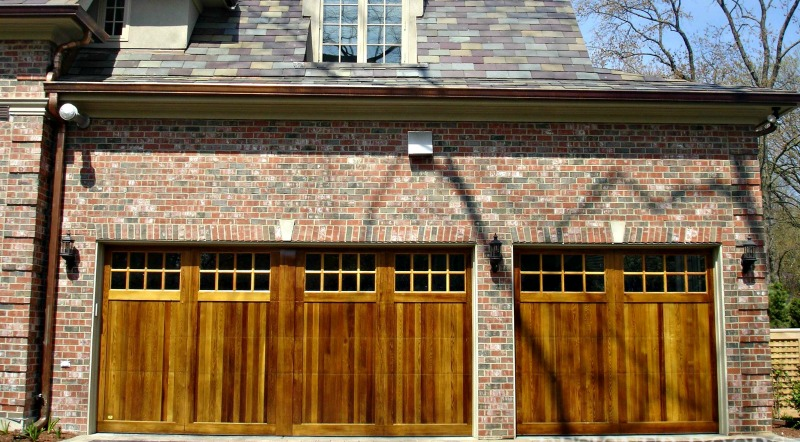 Custom wood garage doors with a simulated center post on the double wide door on the left