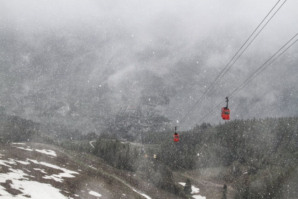 2 red cable carts over the mountain in snow