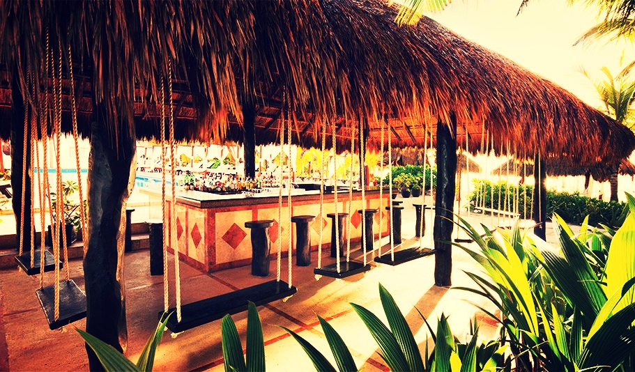COTORROS Enjoy ocean breezes from the comfort of a swing chair while mixologists prepare your favorite drink, in this relaxing open-air palapa bar