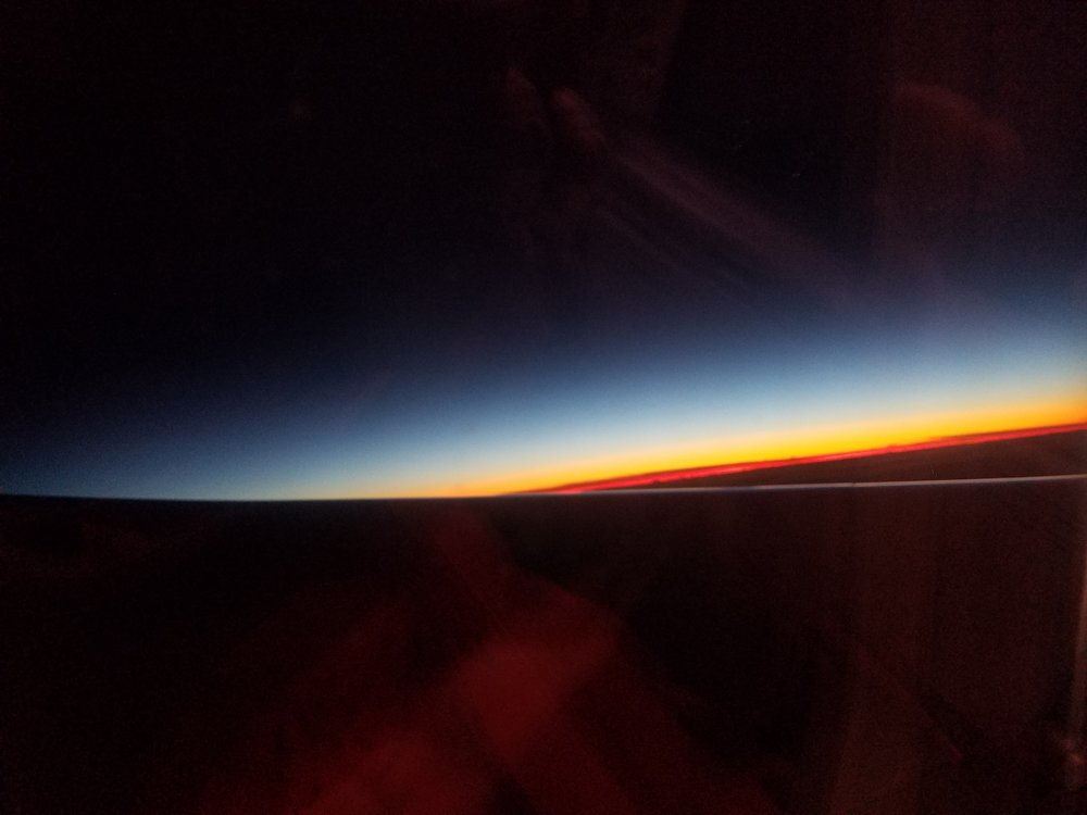 Sunrise over Portugal at midnight EST from tiny plane window