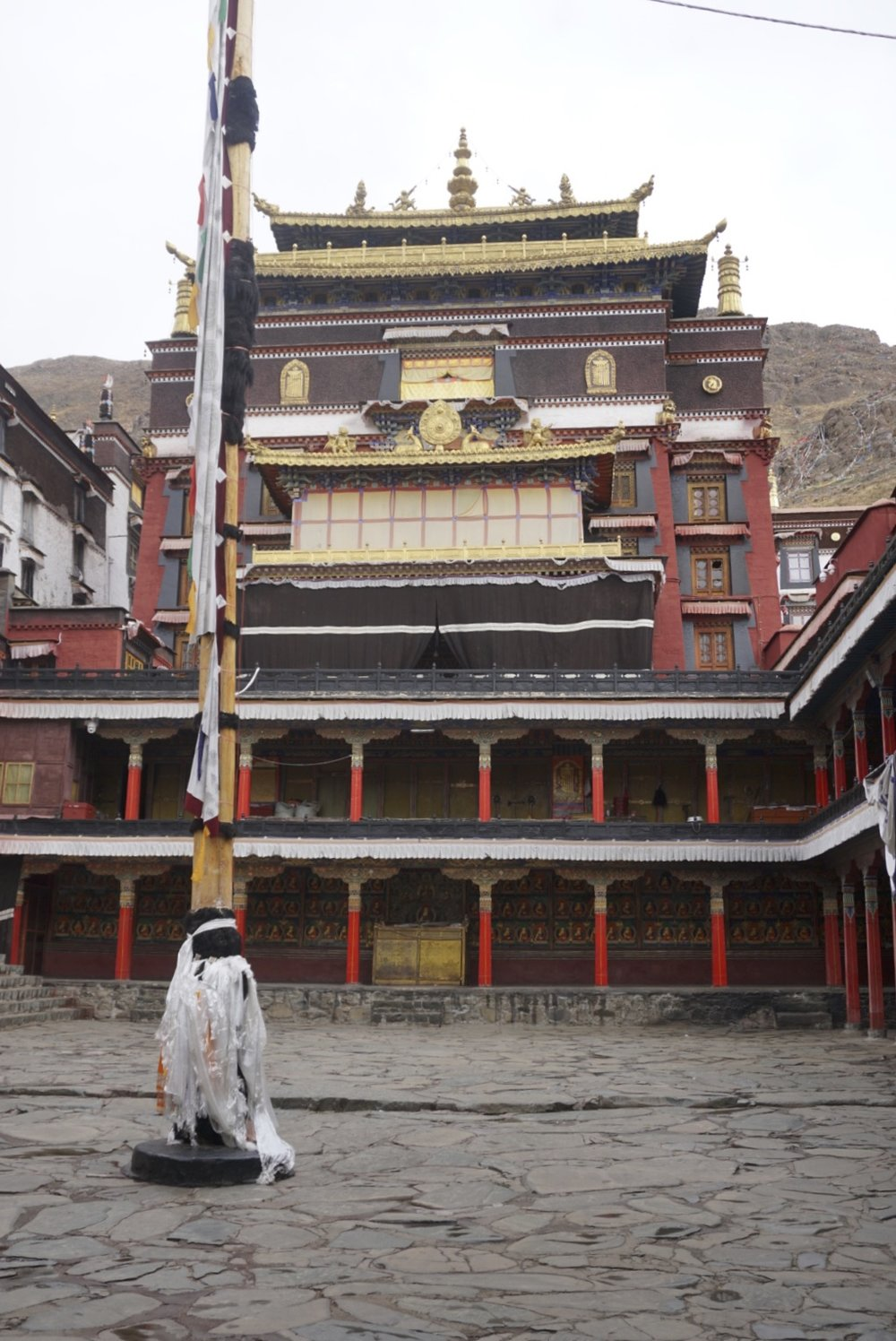 The courtyard of Tashailhunpo monastery witn flagpole in the foreground