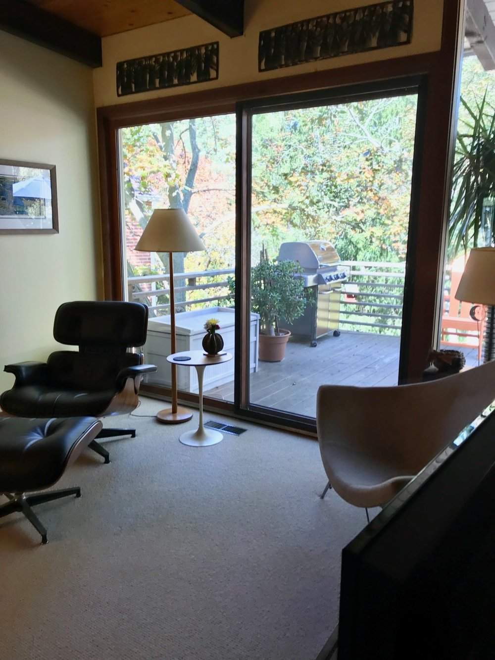 DECK OFF LIVING ROOM WITH EAMES LOUNGE CHAIR