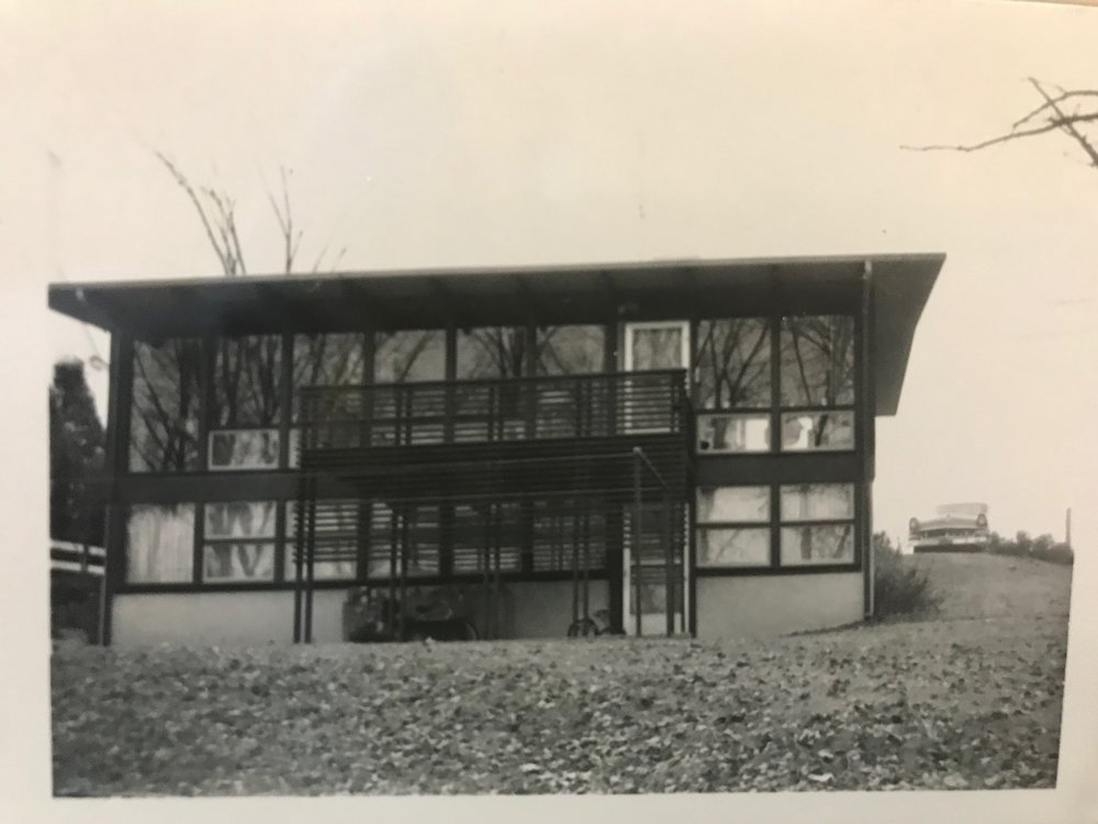 EARLY PHOTO OF TWO STORY WINDOW WALL AND BALCONY