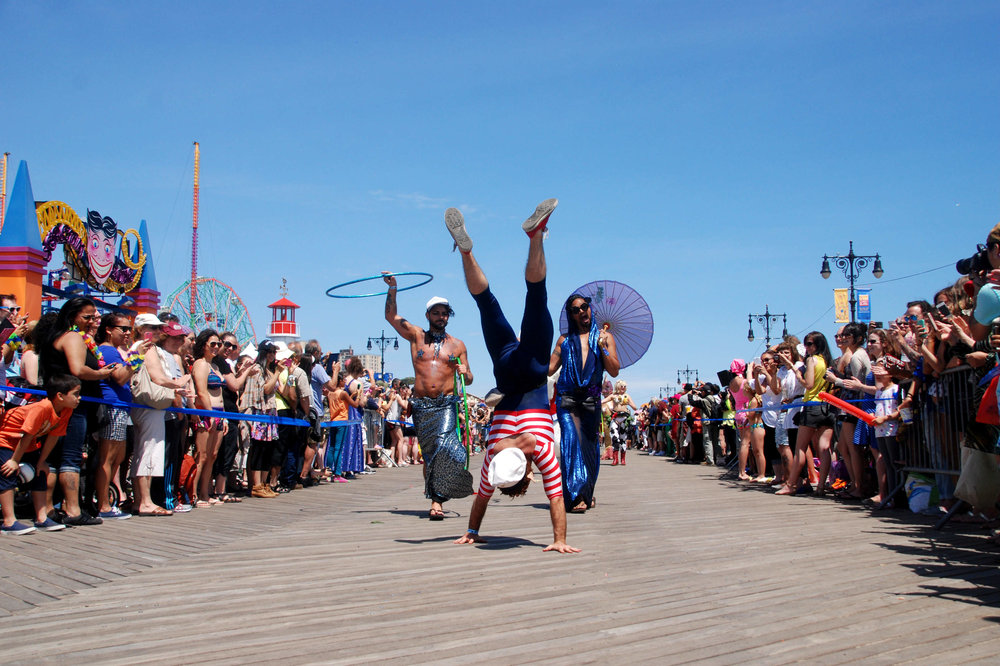 A man does a handstand on the Coney Island boardwalk at the annual Mermaid Parade on June 21, 2014.