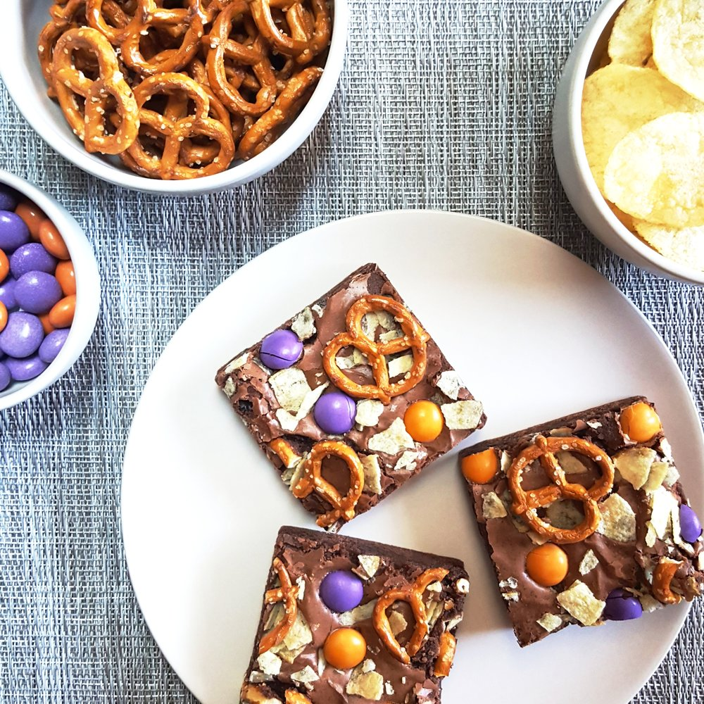 "THE MUNCHIES a junk food lover's dream: our ""got milk?"" brownie topped with salted pretzels, crispy potato chips, and candy coated chocolates. it's the perfect balance between salty and sweet -- and it will satisfy multiple cravings at once."
