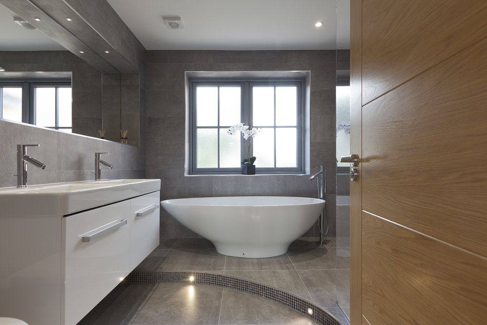 View into the wet room, highlighting curved detail step, freestanding bath and mirrored niche.