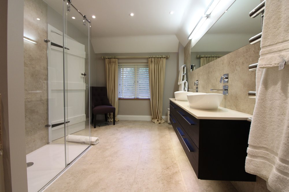 Stunning shower room, with porcelain tiles. Featuring a wall-hung double basin unit and wall mounted taps.