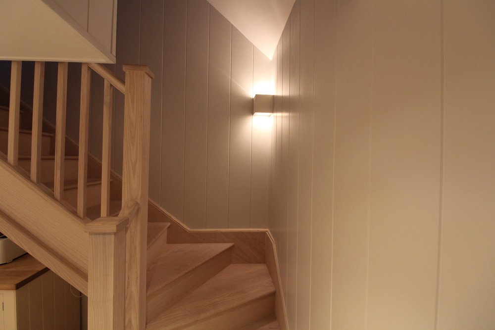 Full height tongue and groove wall panelling. Bespoke ash staircase white washed to give that beach feel.