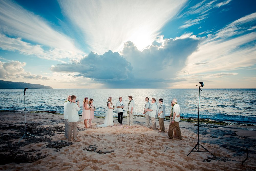 Behind the scenes - sunset beach wedding lit by flashes. To expose correctly for the people, a natural light only image would have left a blown out, all white sky