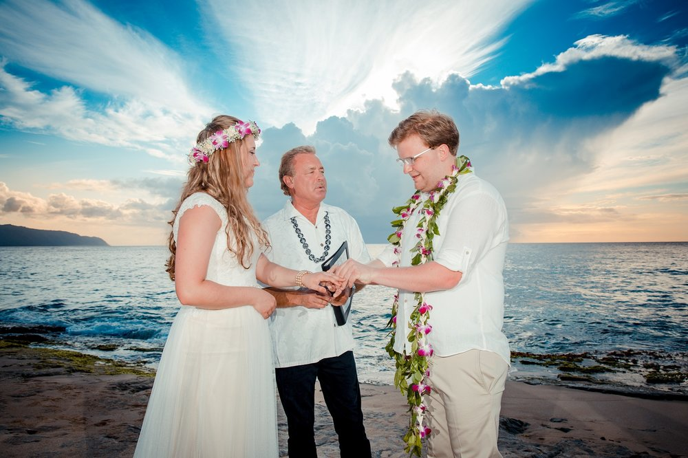 Sunset beach wedding, bride and groom lit softly by flashes