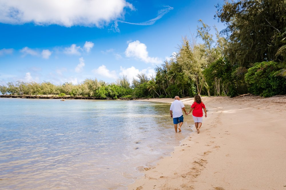 couples anniversary walking on beach oahu portrait