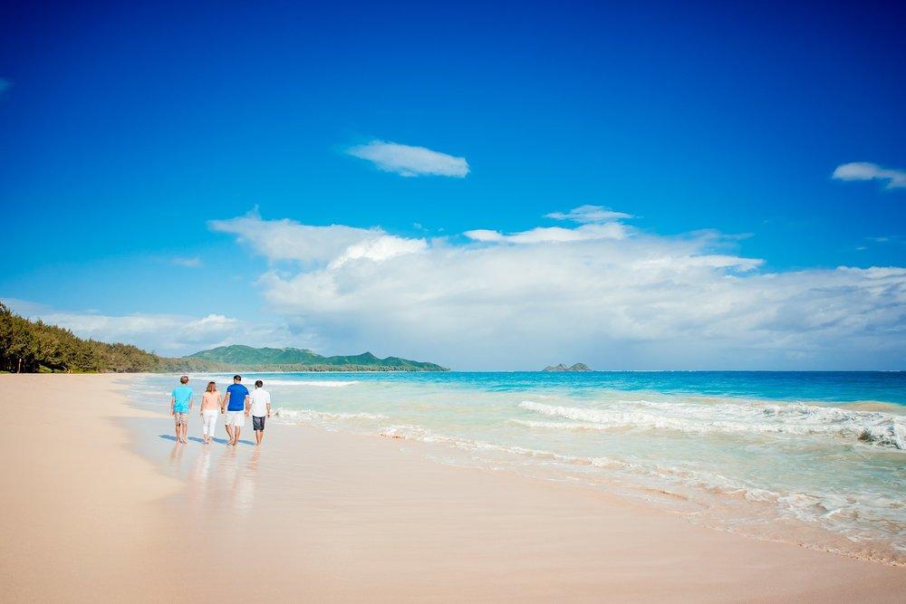 family walking on sunny hawaii beach on oahu