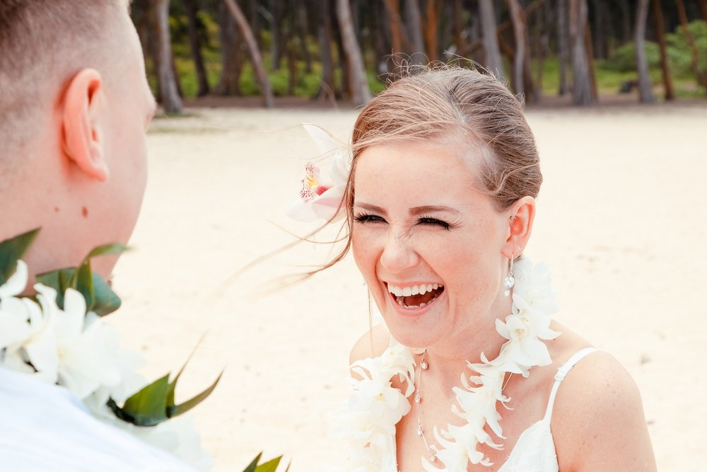 bride laughing during beach wedding ceremony