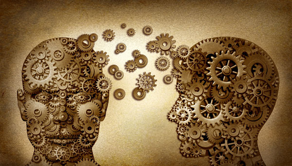 Education and leadership teamwork and lead and learning symbol by two human heads frontal and side view shaped with gears on a grunge old vintage document as an idea made of cogs working together in a team partnership.