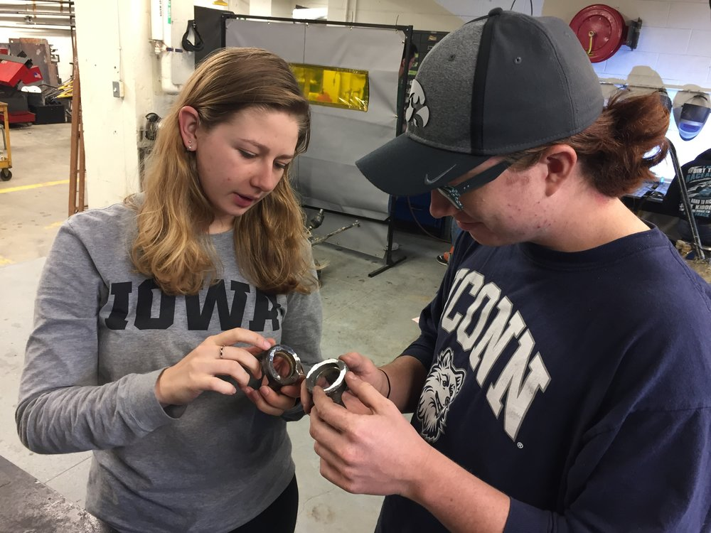 President Kayla Denson and Ben Atzen discuss repairs to a vehicle part.