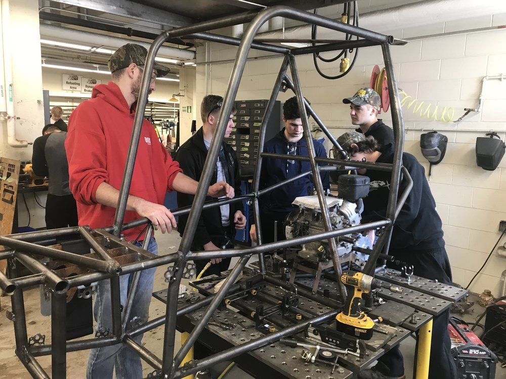 Spencer, Sam, Jake, Rob, and Mitch working on attaching various parts to the new frame for nationals.