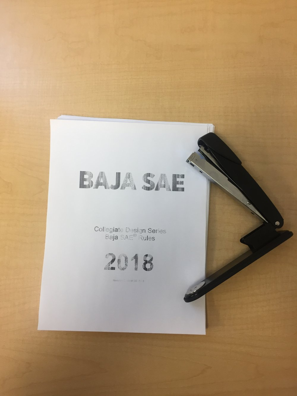 The 116-page 2018 Baja SAE Rulebook next to the now broken stapler