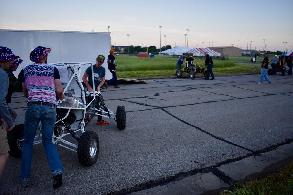 Mitch Evens, Spencer Van Dorn, Ben Atzen, and Kyle Scharm running the car to the Engine Check line.