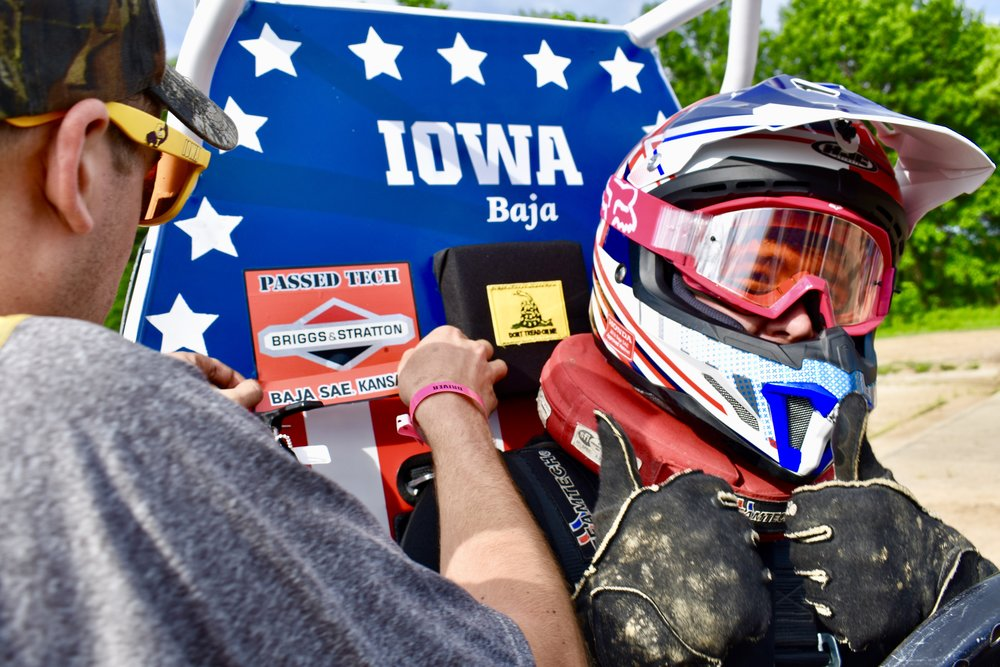 Rob Pohren applying the final tech sticker after Mitch Evens passed the final part of tech inspection (brake check).