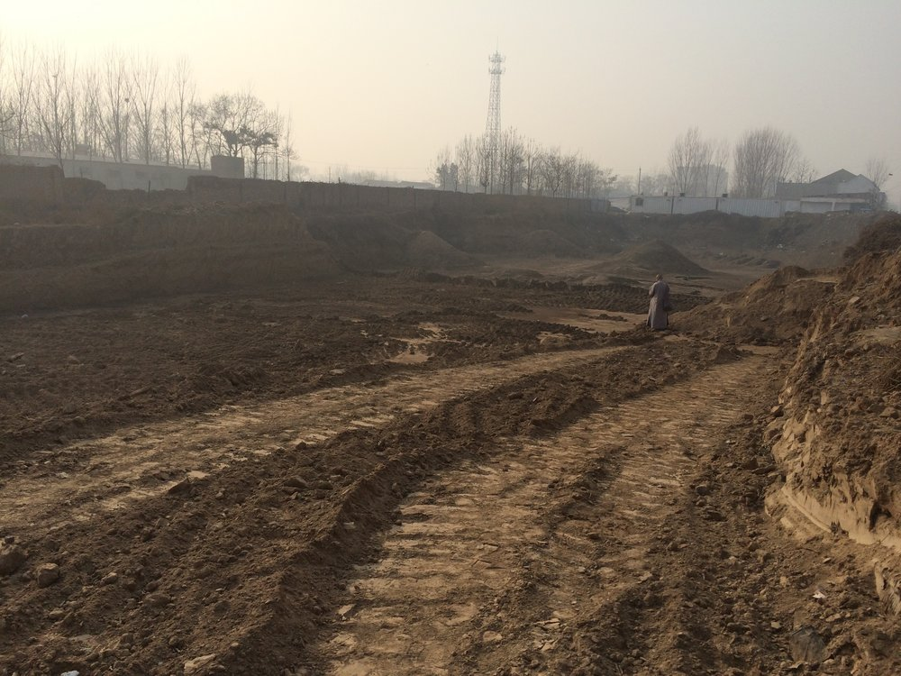 At the behest of the developer, a monk blesses an as-yet undeveloped piece of land that was part of a proposed residential complex in Henan Province.