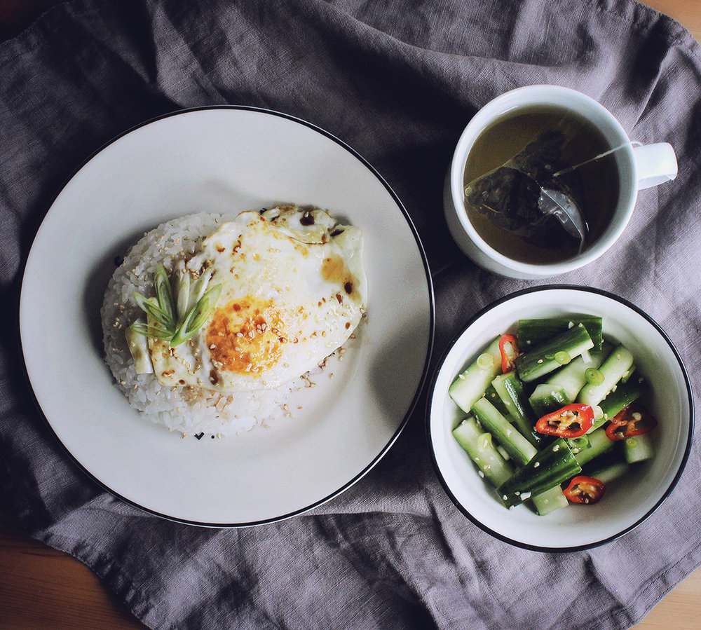 Korean style egg on rice with butter, sesame, soy sauce and spring onion with cucumber pickle on the side / Taiwanese Alishan tea
