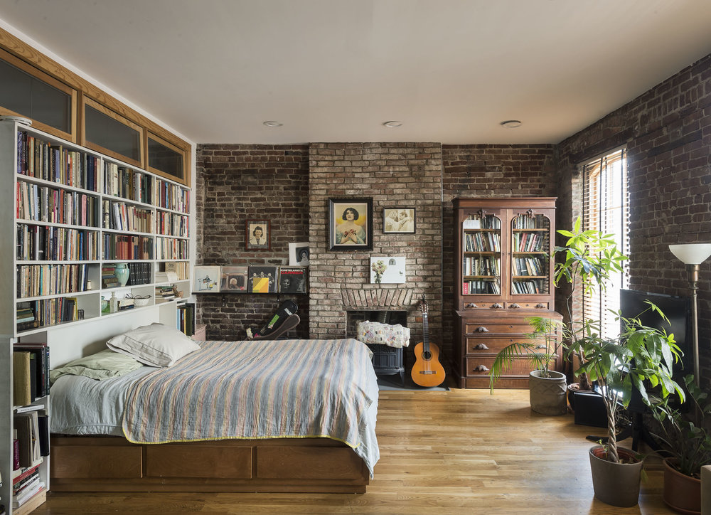 Brick walls, a fireplace, and bookcases in Long Island City, NY. Not the fanciest bedroom, but still a comfy cozy space.(OS)[1000×724]