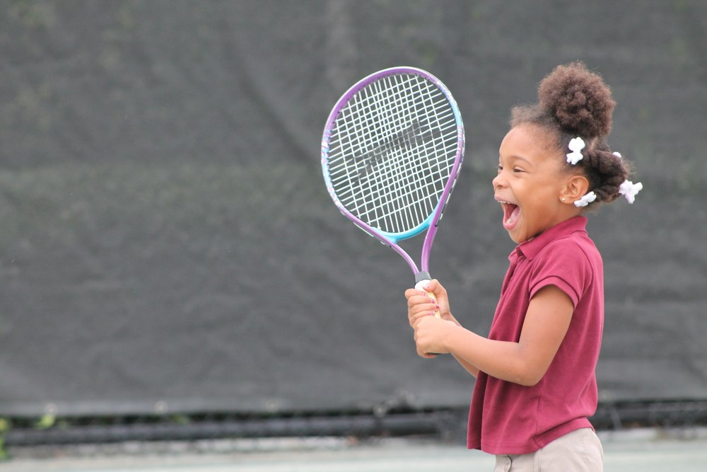 The joy on this little tennis student-mentee's face says it all.