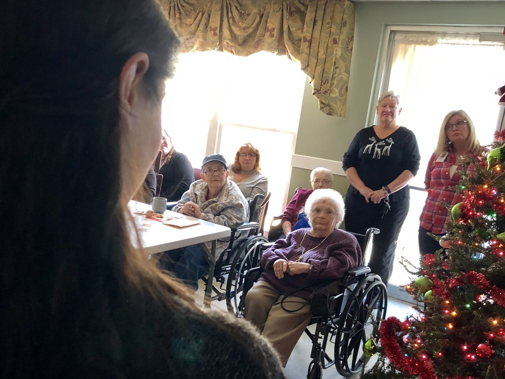 Students present their digital legacy projects at a local nursing home.