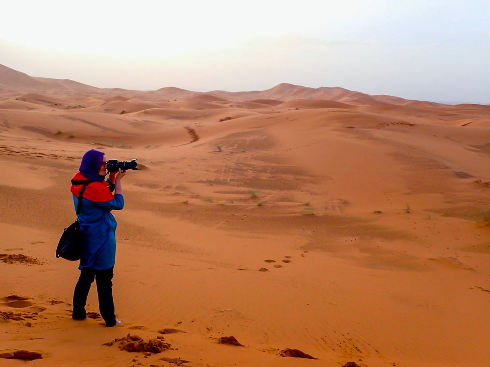 ON THE JOB  — Brea Persing, Goshen, stands on the sand dunes of Morocco zooming in on a sting of camels in the distance. Persing is a photographer who partners with nonprofit organizations and social entrepreneurs to raise awareness for their cause. She also works with businesses in the travel and hospitality industry and teams up with individuals who want a vacation photographer. (Photo Provided)