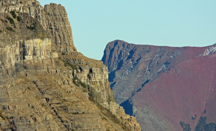 The Empire formation of Going-to-the-Sun Mountain contrasts with the red Grinnell formation of Red Eagle Mountain in Glacier National Park.