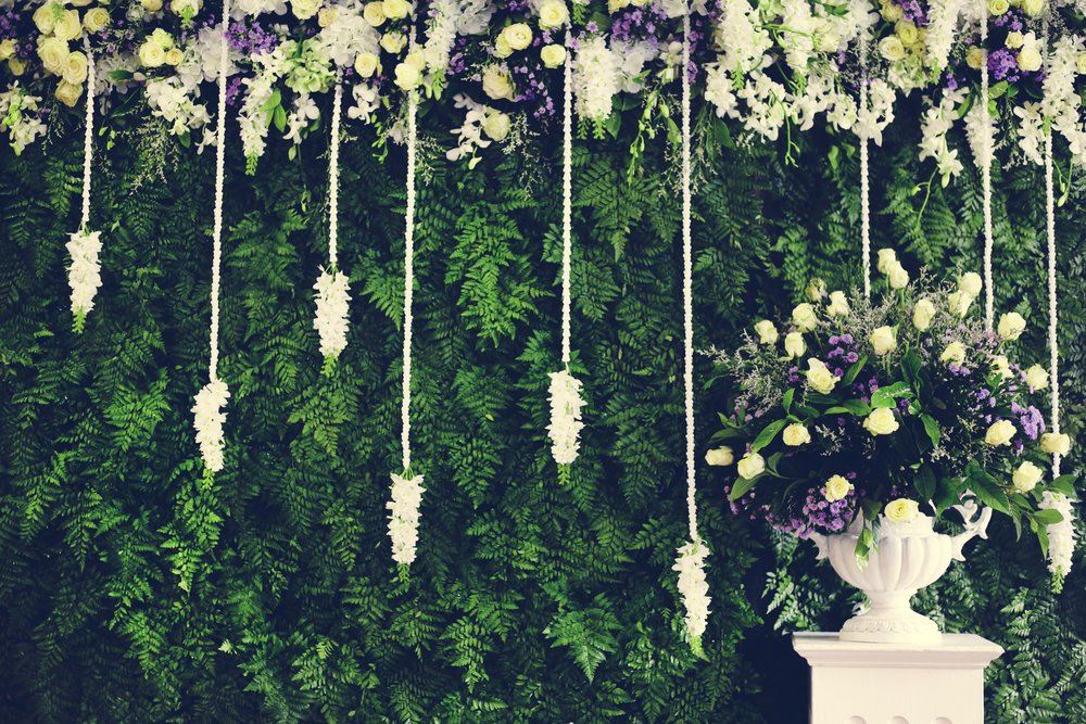 Purple and white flower arrangement on white pedastal with white vine flowers and lilacs greenery wall.jpg