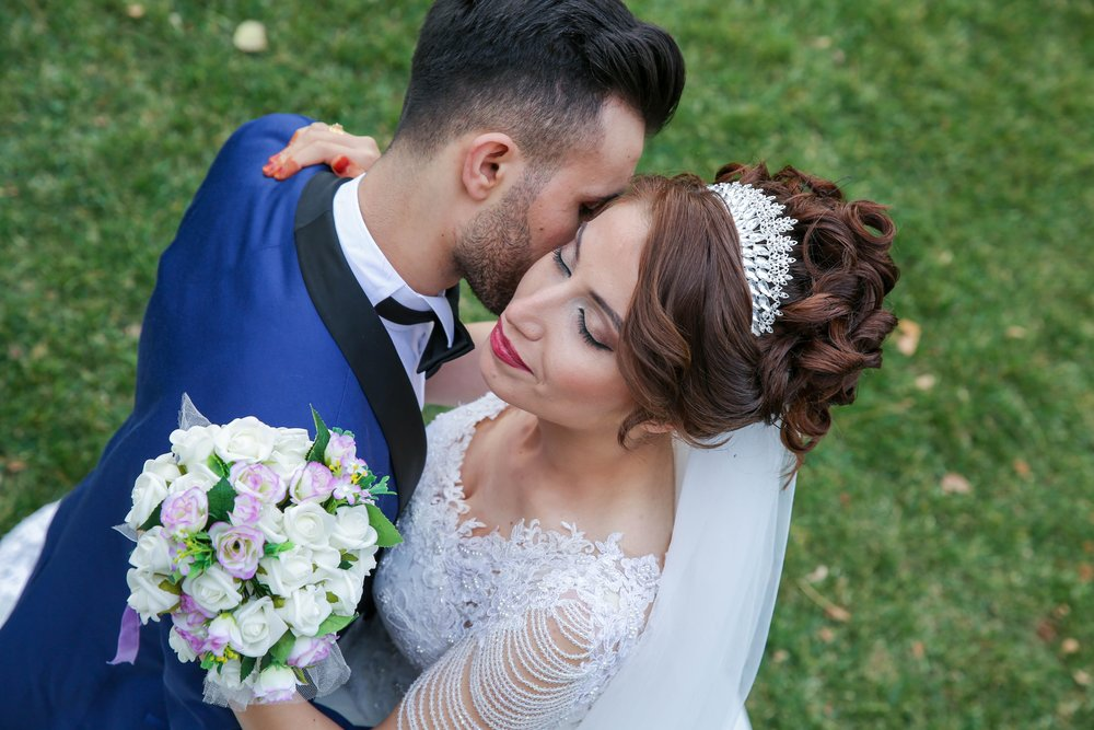 Latino wedding couple groom in blue suit and bride in white dress with boquet of white flowers kissing one another.jpg
