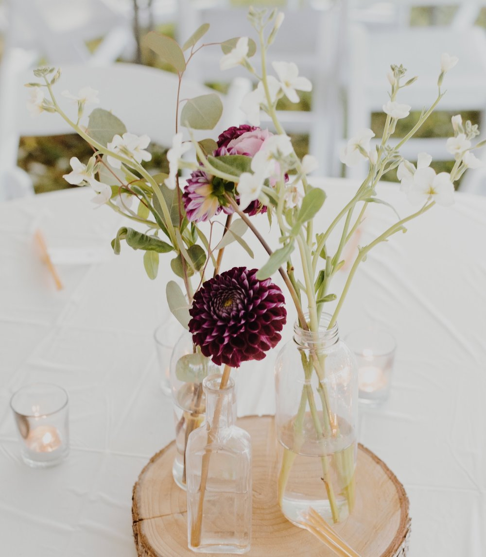 White Linen Table Scape with wood log coaster with purple flowers and greenery and white spring flowers in bottle vases.jpg