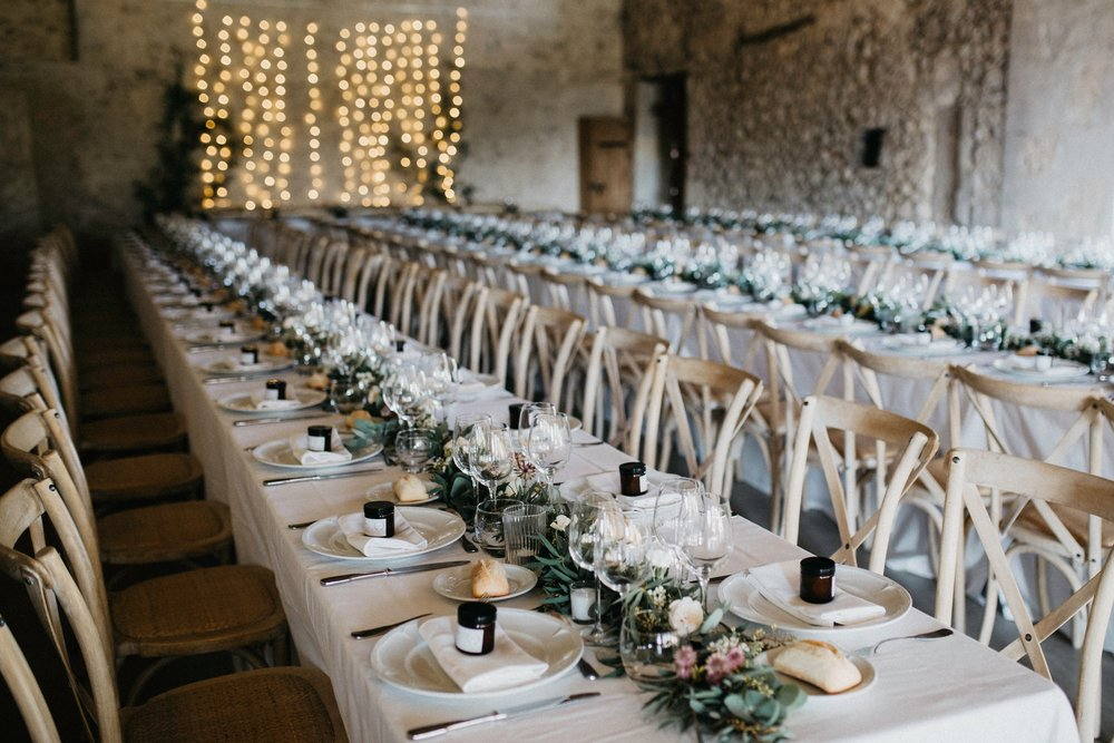 Wedding reception banquet tables with white linen and greenery and purple thistle flowers and table settings with twinkle lights and light stone walls in backgroun.jpg