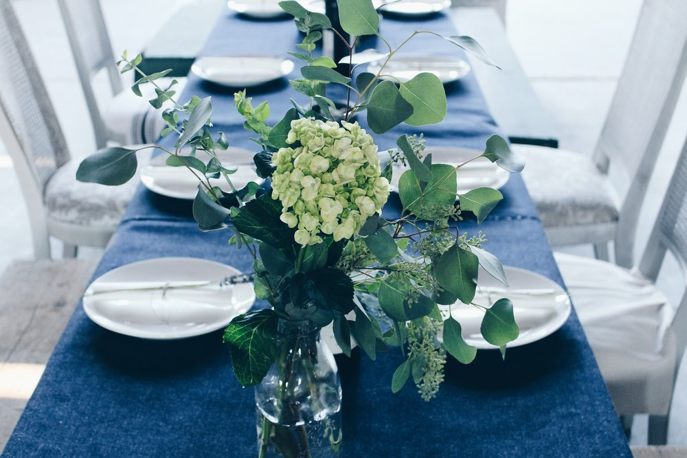 Banquet Table Setting with blue linen and white chairs and white flowers with greenery in bottle vase.jpg