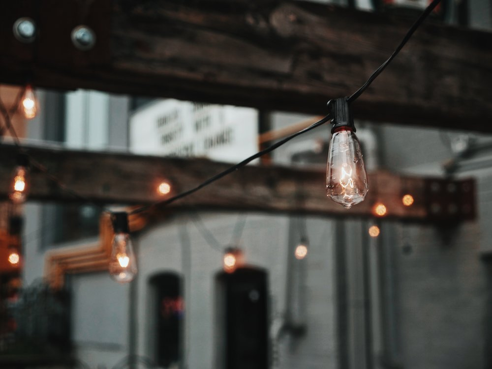 Wedding Lighting With String Edison Bulb Lighting With Wood Beams and White Brick In Background.jpg
