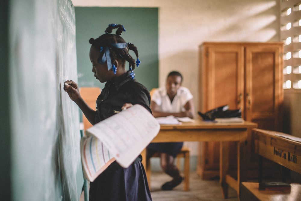 A young girl corrects a fellow students grammar in a classroom in Haiti.