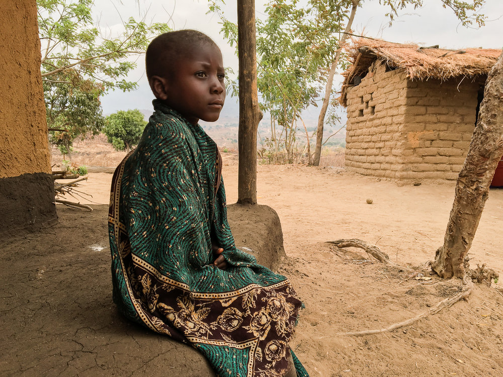 A young Malawian boy sits on his front porch waiting for the sun to rise over the horizon.