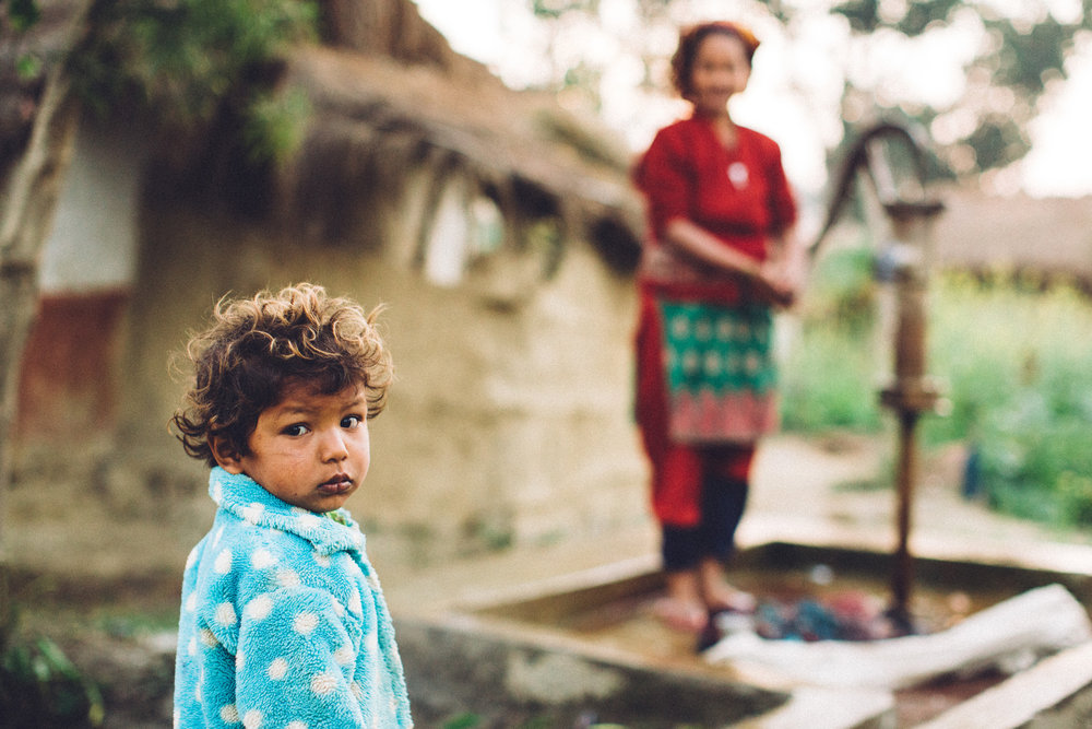 A young child waits for grandmother to pump water in their village in Nepal.