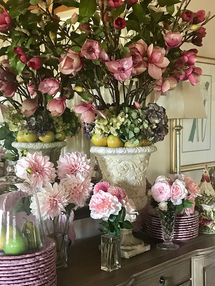 Faux and fresh ballerina pink flowers make for a soft and feminine touch on the buffet table. The pink tones are highlighted next to pink crockery.